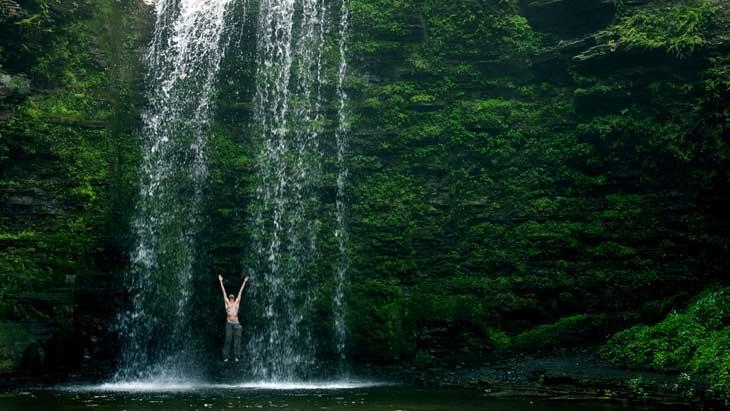 Standing under waterfall