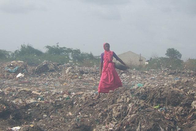 woman walking through landfill
