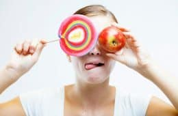 Woman choosing between sweets and apple