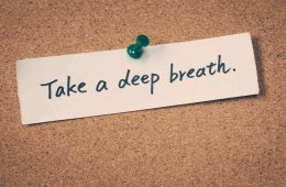 """A paper with the words """"Take a deep breath."""" thumbtacked onto a cork board."""