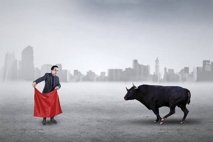 """Businessman with red cloth facing bull - Don't be a """"sacrificial cow"""""""