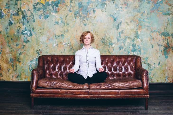 Woman sitting on couch doing breath guided meditation