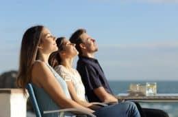 Three friends sitting in chairs on a beach enjoying the sun