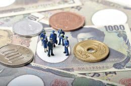 Plastic toy police standing on a selection of banknotes and coins