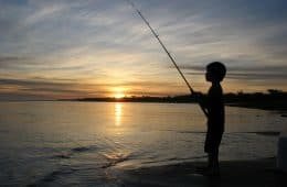 Boy fishing at sunset