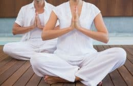 couple in white sitting in a lotus position