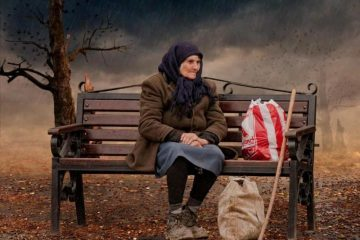 Old woman sitting on bench with shopping bags