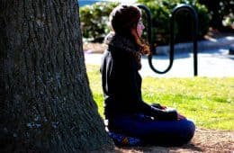 Young woman meditating beside tree trunk - Mindful breathing