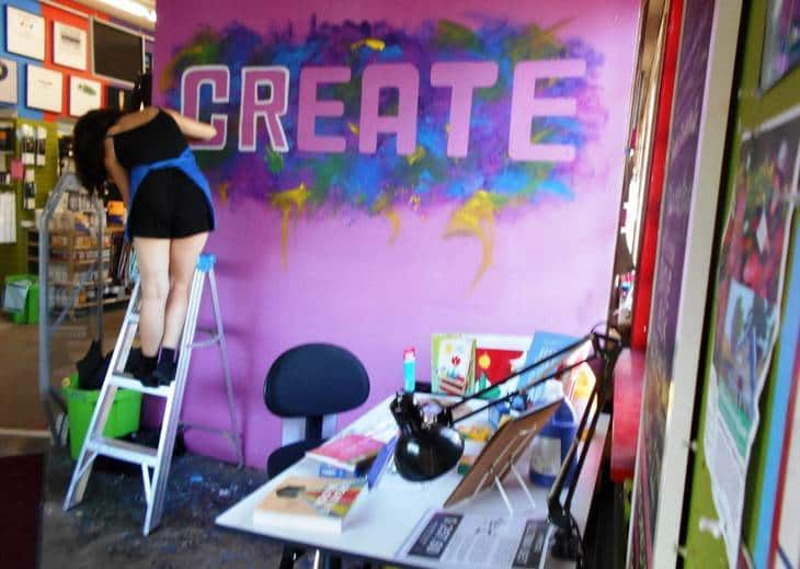 Woman painting the word create on a wall -