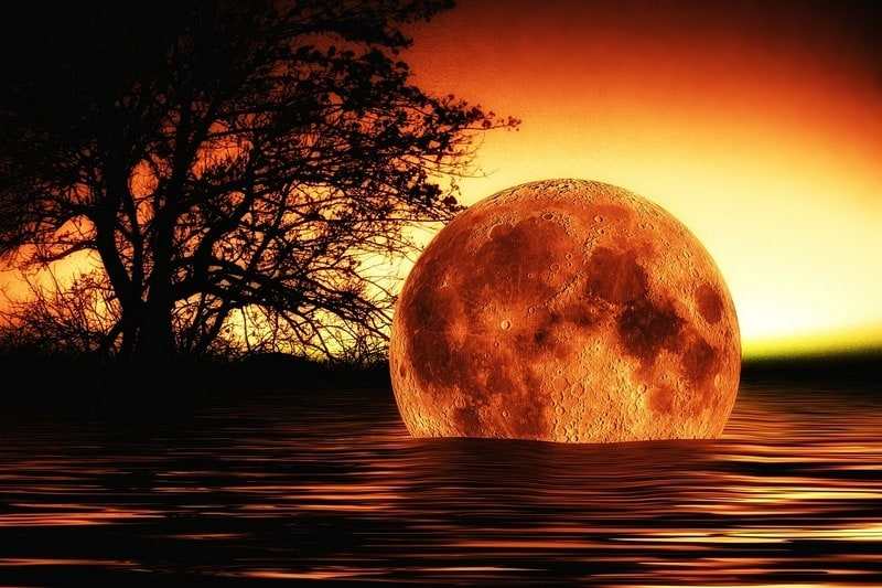Moon descending into a lake at sunset