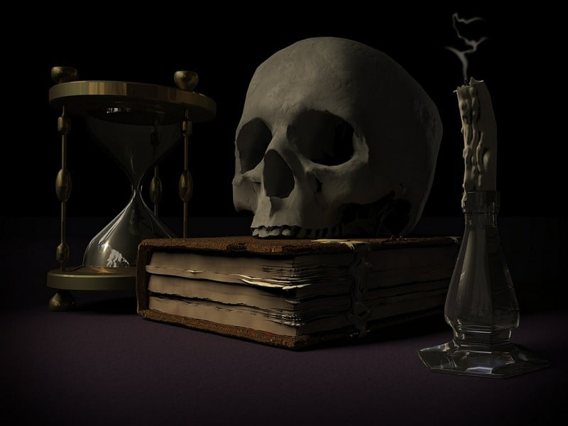 collage of a skull on top of a book with an hourglass and a snuffed out candle