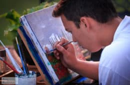 Young man painting - The Artist's Way turns 25