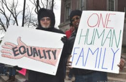 White man and black man with signs on U.S. Human Rights Day - Unexpected encounter