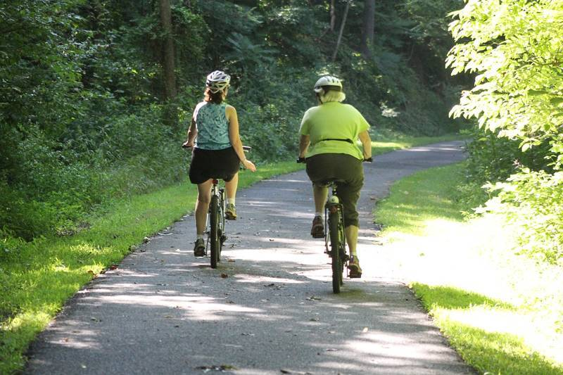 Middle-aged couple biking on paved trail - Becoming a master of healthy living