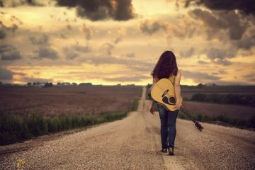 Girl with guitar on road