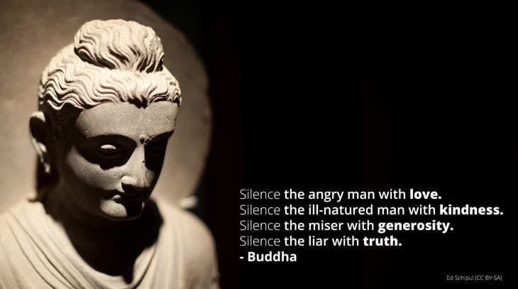 Buddha statue with quote on silencing anger, greed, etc