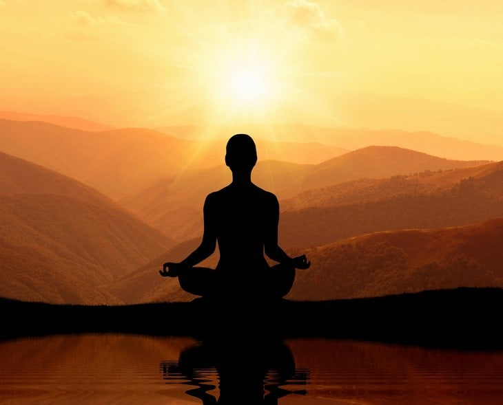 Man meditating in mountains - meditation tips