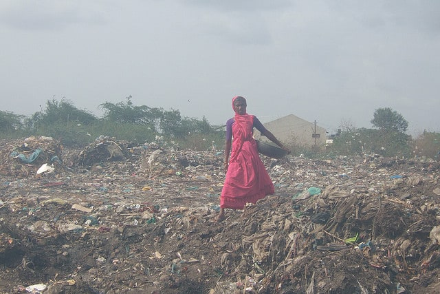 woman walking through landfill