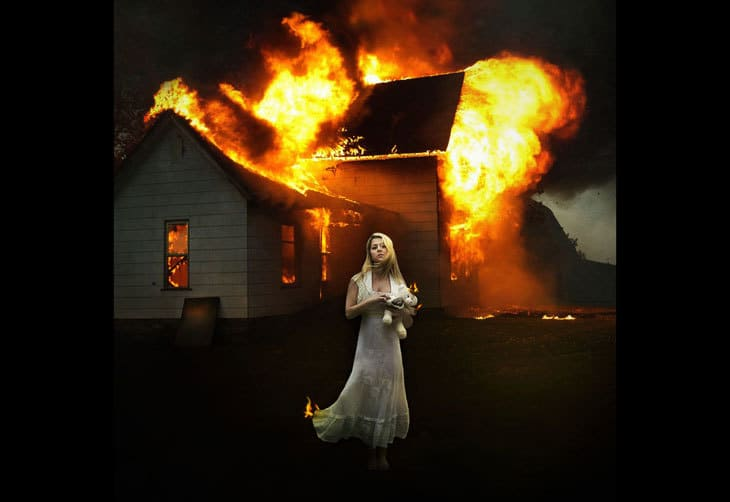 Woman in front of burning house - compassion