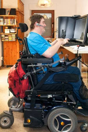 Man in wheelchair on computer - Empowering people with disabilities