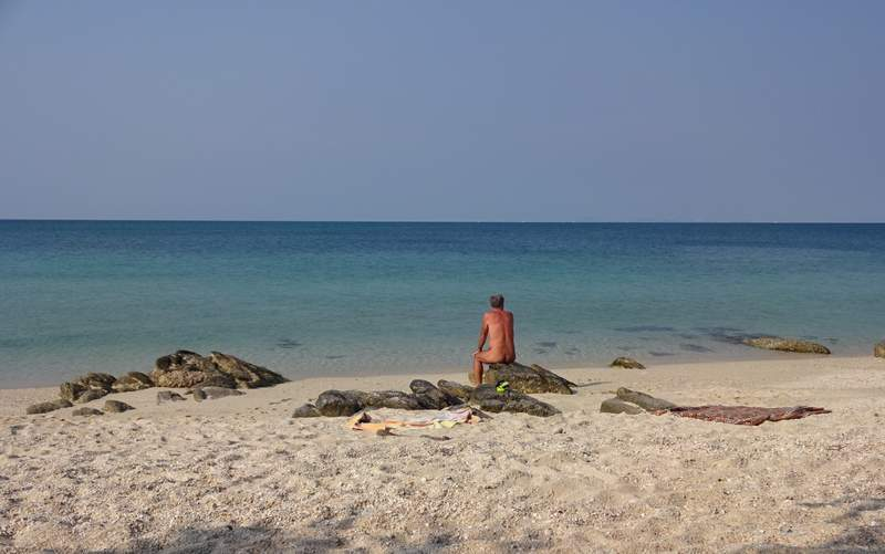 Man sitting alone on a rock, staring at the sea