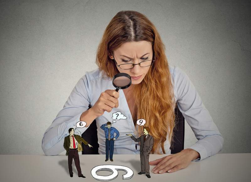 Woman with magnifying glass looking at three men standing on table