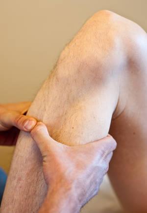 Osteopath holding leg - Healing through bodywork