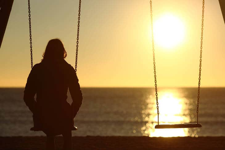 Woman alone on swing - Being alone and still