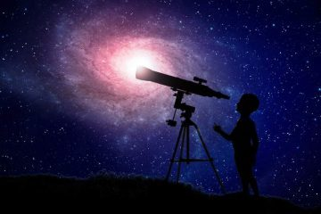 Young boy looking at the stars through a telescope