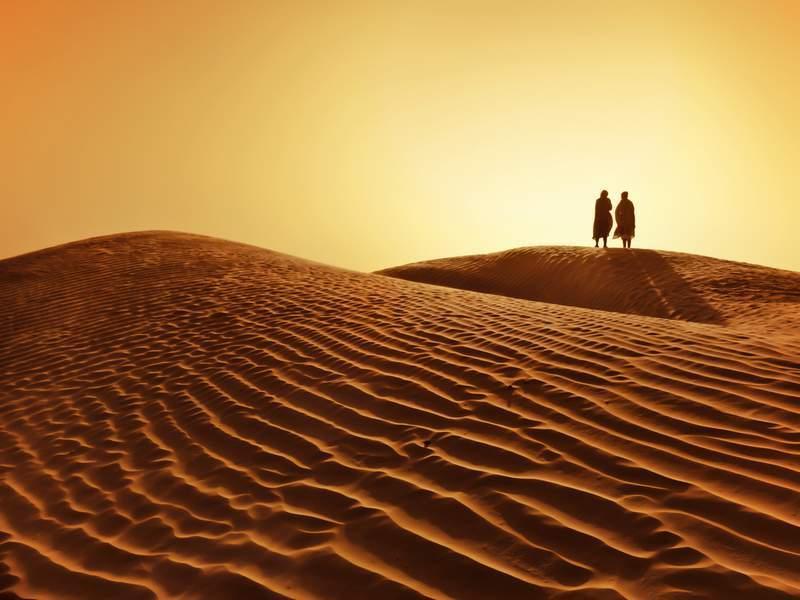 Couple walking in the Sahara Desert