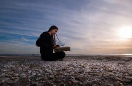 woman with a musical instrument sitting on the beach