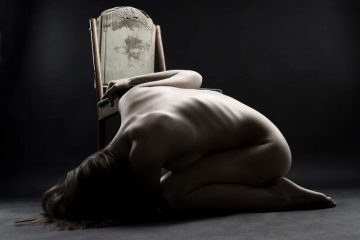 Naked woman curled up on the floor crying