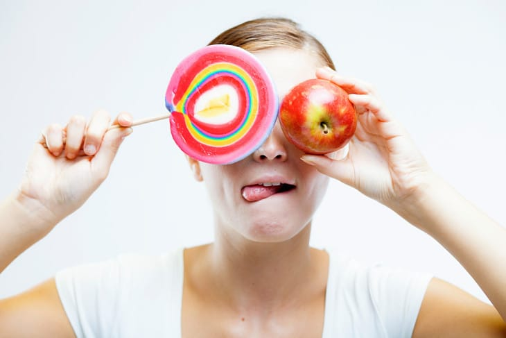 Woman choosing between sweets and apple