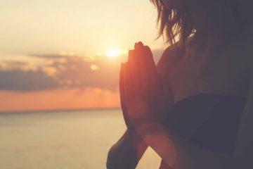 Woman praying at sunrise on beach