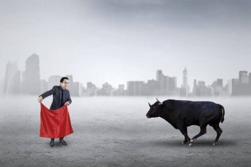 "Businessman with red cloth facing bull - Don't be a ""sacrificial cow"""