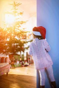 http://www.shutterstock.com/pic-331509089/stock-photo-christmas-morning-a-little-girl-in-pajamas-wearing-a-santa-claus-hat-opens-the-living-room-door.html?src=tuAHSSTJkCpiiAjI1ufJVw-5-68