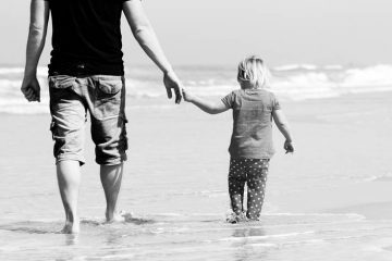 Father and daughter wading at beach - Poems by Ryan Warren