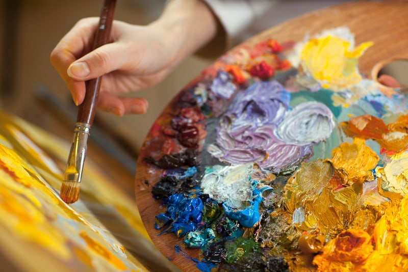 artists hand with brush, palette and oils