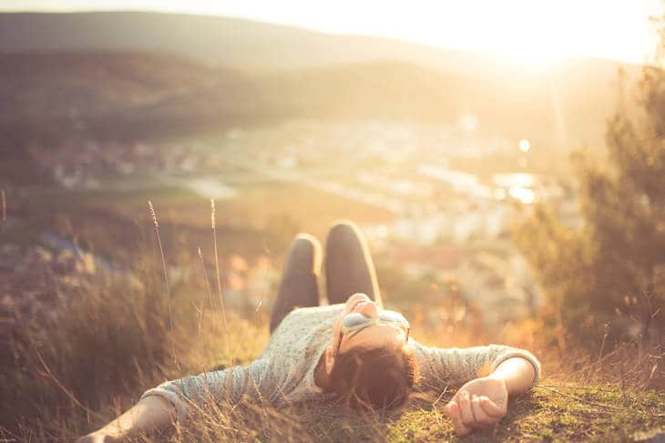 Woman lying down at mountaintop - Life in