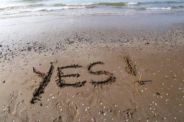 The word yes in the sand
