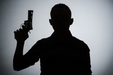 Silhouette of man with gun