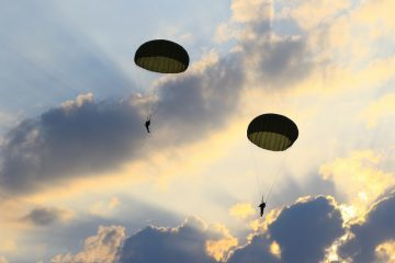 Parachutists in partly cloudy sky with sun rays