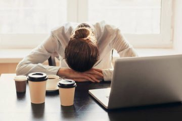 Woman with coffee stressed out at desk - The Vitality Map excerpt