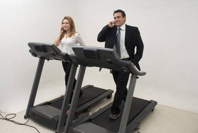 Businessman and businesswoman on treadmill with cell phones - The Vitality Map excerpt