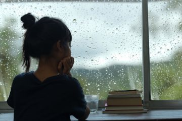 Young girl sitting at the window watching the rain