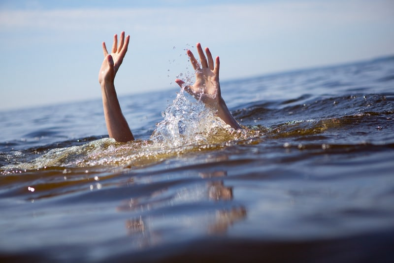 person drowning holding hands above water for help