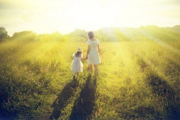 mother and daughter walking in sunlit meadow