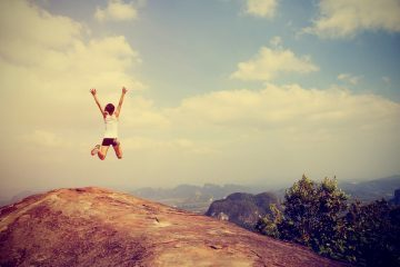 Young Asian woman jumping for joy on top of mountain