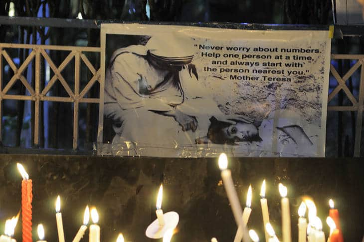 Candlelight vigil with Mother Teresa quote banner - Humour heals