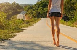 Woman walking on road barefoot